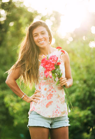 Beautiful Young Woman with Flowers in Countryside, Summer Lifestyle photo
