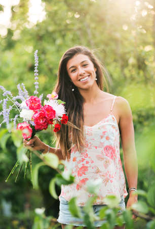 a serene life: Beautiful Young Woman Smelling Flowers in Nature, Summer Lifestyle Stock Photo