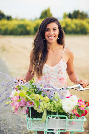 Beautiful Young Woman on Bike in Countryside, Summer Lifestyle  photo