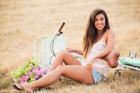 Beautiful Smiling Girl Sitting next to bike in Countryside, Summer Lifestyle  photo