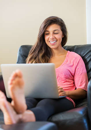 young beautiful happy woman using a laptop computer at home photo