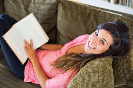 beautiful happy young woman reading a book sitting on a sofa in a living-room photo