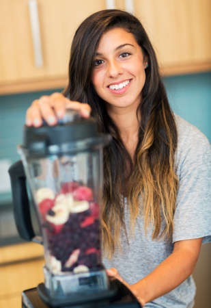 Beautiful Young Woman Making Fruit Smoothie in Blender photo