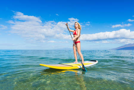 surfing: Attractive Woman on Stand Up Paddle Board, SUP, Tropical Blue Ocean, Hawaii