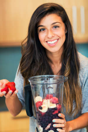 food processor: Beautiful Young Woman Making Fruit Smoothie in Blender
