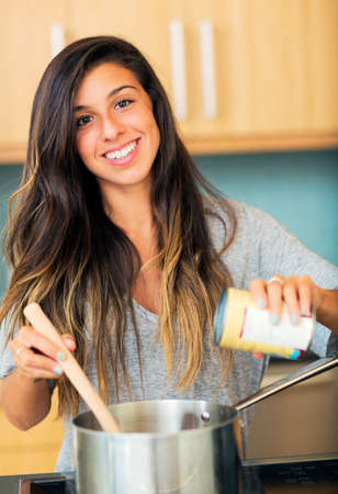 Beautiful Young Woman Cooking Dinner at Home In Kitchen, Lifestyle Concept photo