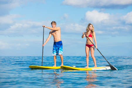 Attractive Couple Stand Up Paddling in Hawaii photo