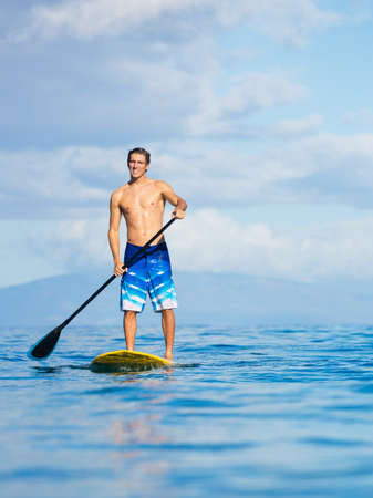 paddleboard: Attractive Man on Stand Up Paddle Board, SUP, Tropical Blue Ocean, Hawaii Stock Photo