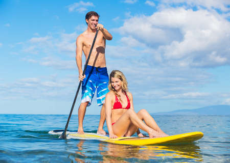 Attractive Couple Sharring Stand Up Paddle Board, Hawaii Stock Photo