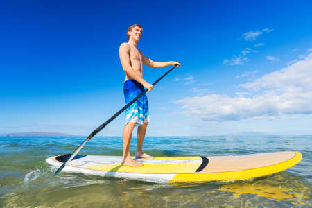 Attractive Man on Stand Up Paddle Board, SUP, Tropical Blue Ocean, Hawaii photo