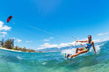 Attraktive junge Frau KiteBoarding, Spaß im Ozean, Extremsport Kitesurfen
