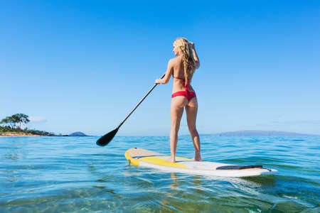 Young Attractive Woman on Stand Up Paddle Board, SUP, in the Blue Waters off Hawaii, Active Life Concept Imagens - 22168256