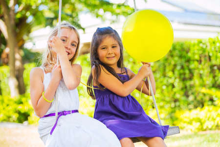 Happy little Girls Playing on Swing photo