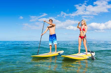 ハワイでは、アクティブな生活概念パドリング魅力的なカップルに立ち上がる
