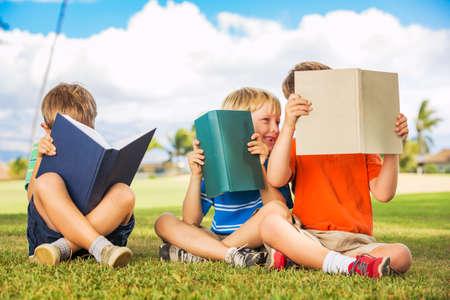 Groep van Happy Kids Boeken lezen buiten, Vriendschap en Leren Concept Stockfoto
