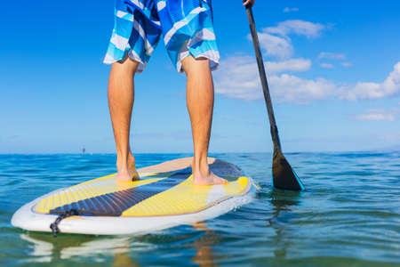 若い魅力的な基板上にマン スタンド アップ パドル、青いハワイ沖で SUP