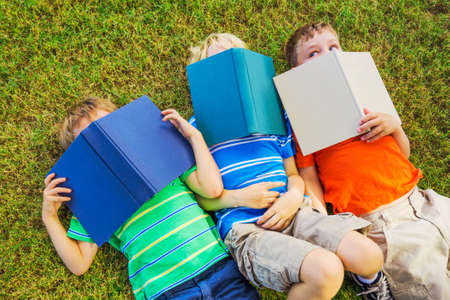 book: Group of Happy Kids Reading Books Outside, Friendship and Learning Concept