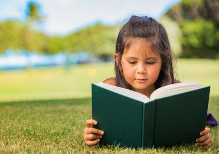 deitado: Menina bonito do livro de leitura fora na grama