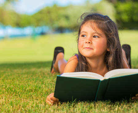 schoolgirls: Cute Little Girl Reading Book Outside on Grass Stock Photo