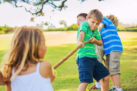 Groep van gelukkige jonge kinderen spelen touwtrekken Buiten op het gras Stockfoto