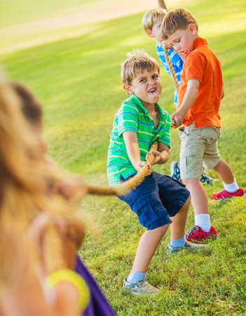 Group of Happy Young Children Playing Tug oF War Outside on Grass photo