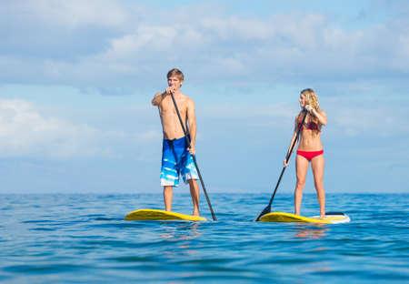 魅力的なカップルがハワイでアクティブ ライフ コンセプト パドリング立ち上がる 写真素材