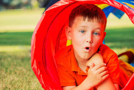 Cute Young Boy Playing Outside in Colorful Tunnel photo