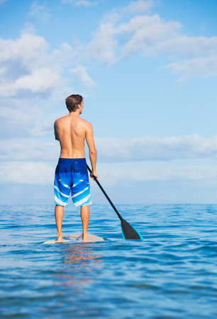 Young Attractive Mann on Stand Up Paddle Board, SUP, in the Blue Waters off Hawaii, Active Life Concept Stock Photo