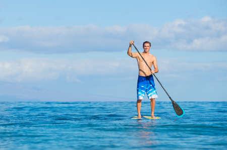 Junge Attraktive Mann am Stand Up Paddle Board, SUP, im Blue Waters aus Hawaii, Freizeit-Konzept