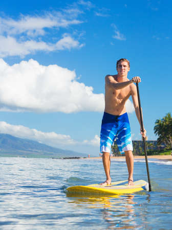 Young Attractive Mann on Stand Up Paddle Board, SUP, in the Blue Waters off Hawaii, Active Life Concept photo