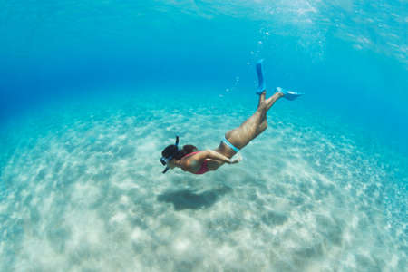 Underwater image of a woman snorkeling in tropical sea over sandy bottom