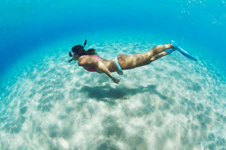 free diving: Underwater image of a woman snorkeling in tropical sea over sandy bottom