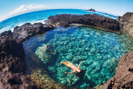 sensory perception: Attractive young woman floating in beautiful ethereal natural pool