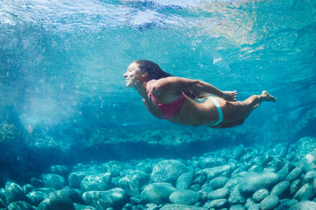 Attractive young woman floating in beautiful ethereal natural ocean pool, Underwater View photo