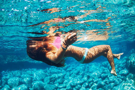 Attractive young woman floating in beautiful ethereal natural ocean pool, Underwater View