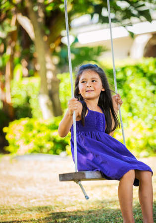 Cute Little Girl Playing on Swingset