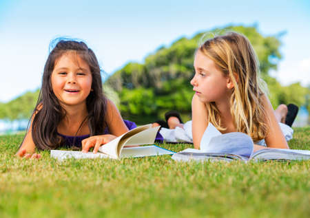 Cute Little Girls Reading Books Outside on Grass after School photo