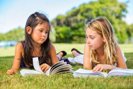 cute little girls: Cute Little Girls Reading Books afuera en hierba despu�s de la escuela