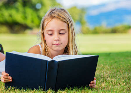 Cute Little Girl Reading Outside on Grass photo