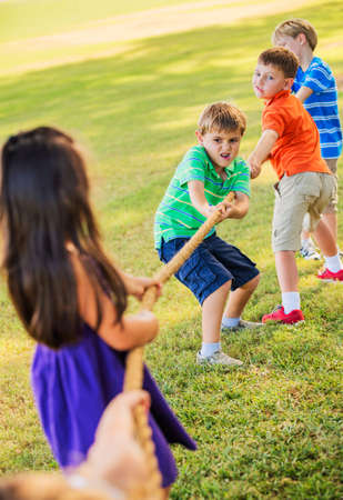 Group of Kids Playing Tug of War On Grass Stock Photo