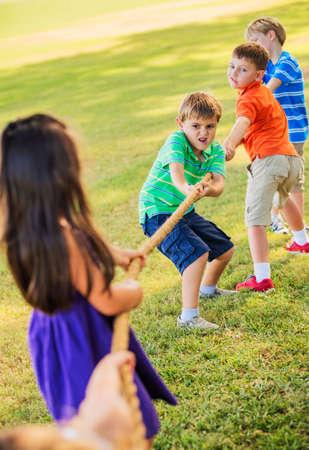 ni�os jugando parque: Grupo de ni�os jugando tira y afloja en la hierba Foto de archivo