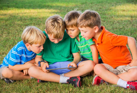 internet school: Group of Kids Sitting on grass and using tablet computer