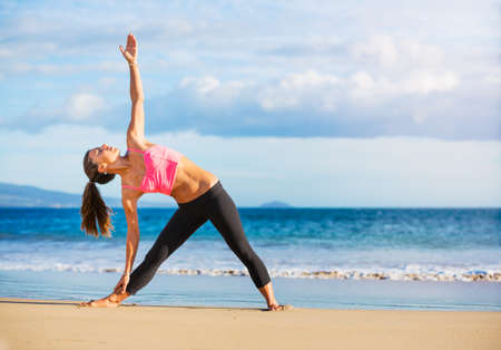 thai yoga: Young woman practicing yoga on the beach at sunset