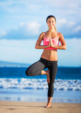 Young woman practicing yoga on the beach at sunset Stock Photo - 22416578