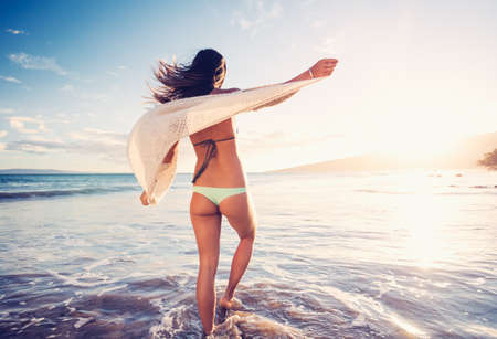 woman beach: Young woman walking on a sandy beach at Sunset, Dreamy Lighting Stock Photo