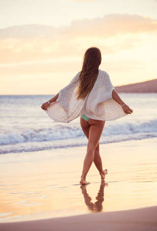 Young woman walking on a sandy beach at Sunset, Dreamy Lighting photo