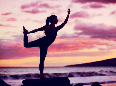 Silhouette young woman practicing yoga on the beach at sunset Stock Photo - 22366459
