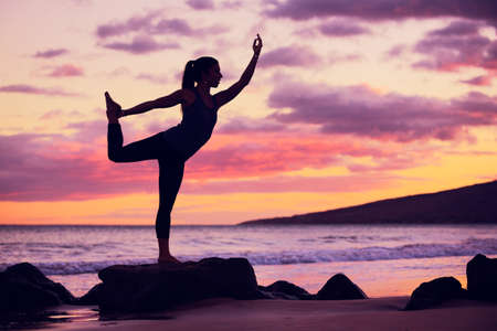 mind body spirit: Silhouette young woman practicing yoga on the beach at sunset Stock Photo