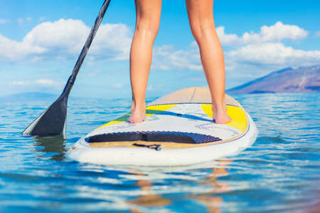 Attractive Young Woman Stand Up Paddle Surfing In Hawaii, Beautiful Tropical Ocean, Active Beach Lifestyle Stock Photo