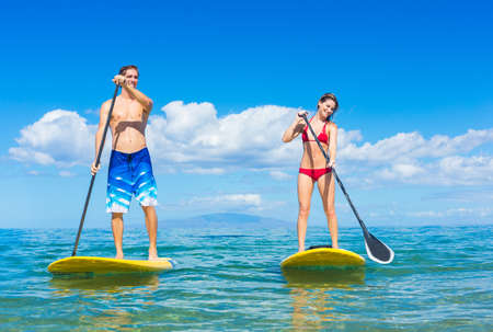 Couple Stand Up Paddle Surfing In Hawaii, Beautiful Tropical Ocean, Active Beach Lifestyle Foto de archivo
